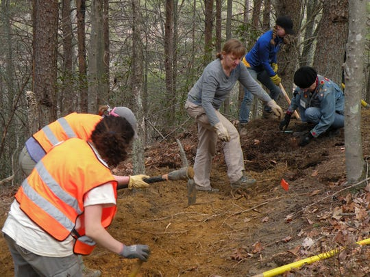 Workers, including Cathy Lamb, center, of Chattanooga, deal with clearing roots along the Cumberland Trail.