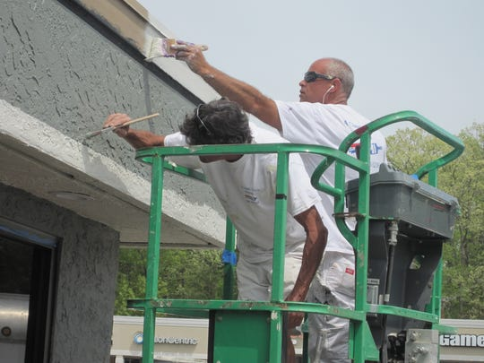 Ray Streeter (left) and Steve Daliso paint the exterior of the Taco Bell on Clemson Boulevard on Wednesday afternoon.