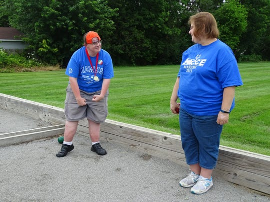 "Tony Nicolosi flexes his arms after throwing a good shot in bocce against his sister Tina Cain. ""Not the least bit competitive,"" Cain says sarcastically of her brother."