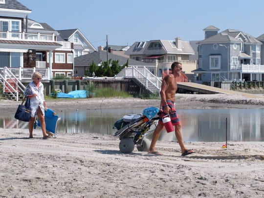 Beachgoers cross over one of numerous large pools of