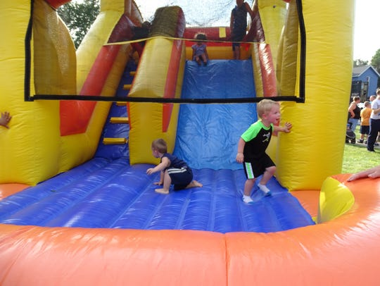 Kids play on the inflatable slides and bounce houses