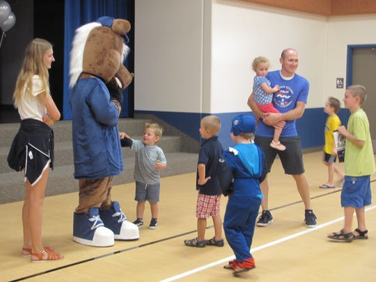 Children visit with the Mustang mascot at the new Majestic