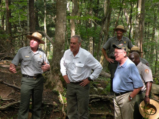U.S. Interior Secretary Ryan Zinke, center, and Sen. Lamar Alexander, right, listen to ranger Tobias Miller talk about a rehabilitation project on Rainbow Falls Trail in the Great Smoky Mountains National Park.