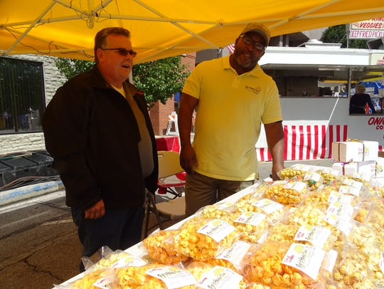 Rodney Robertson, right, owns Marion-based Pop'd Sensations, which sold a variety of popcorn at the 2017 Popcorn Festival.