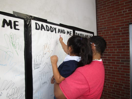 """Fathers and their children were invited to trace each other's hand prints on large sheets of paper at """"Walk and Talk With Dads"""" at School 2."""