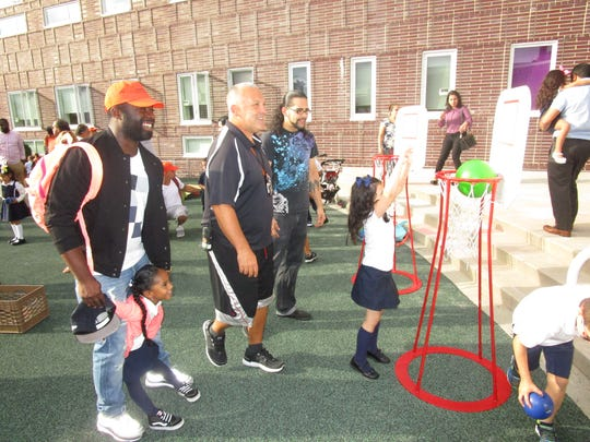 """School 2 physical education teacher Frank Green, center, playing with fathers and their kids at the start of """"Walk and Talk With Dads"""" at School 2 in Linden."""