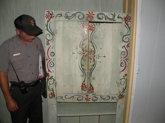 Historic Preservation Director Randy Hatten stands beside a cabinet repainted to match its original design in the Historic Elkmont District.