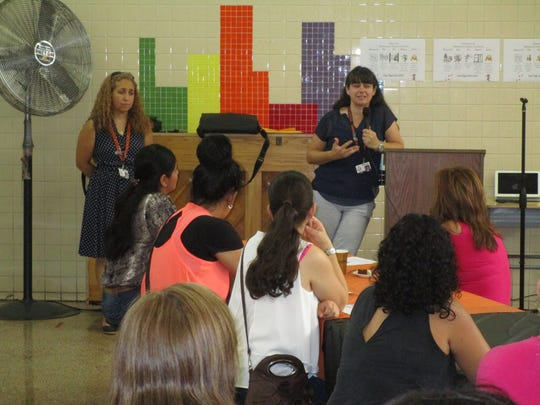 English as a Second Language teacher Mercedes Fernandez, left, and bilingual teacher Sandra Hernandez talking to Spanish-speaking parents who were invited to School No. 2 on Wednesday, Sept. 20, to learn more about programs available to their children and to them throughout the district.