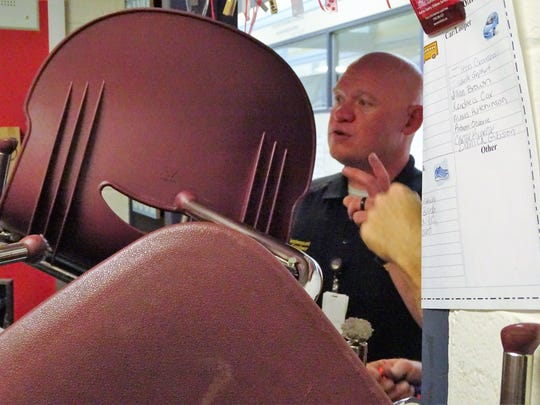 Marion City Police Lt. BJ Gruber peers through a makeshift barricade during active shooter training Wednesday at Benjamin Harrison Elementary School.