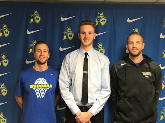 Mark Mettie (center), recently signed to play college basketball at Madonna University. Flanking him on signing day are Crusaders' associate coach Adam Kerfoot (left) and head coach Noel Emenhiser (right).