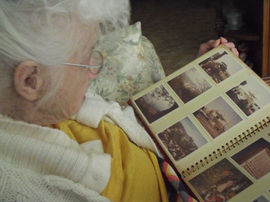 Erma Eash looks over a scrapbook of memories relating to Eash Quality Feeds, now named Findley Feeds.