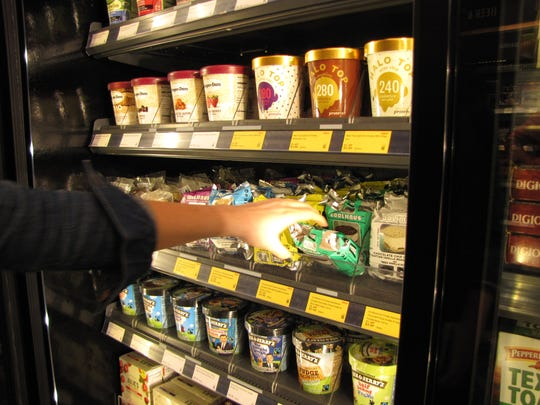 A woman buying ice cream at the Amazon Go convenience store at Amazon's headquarters in Seattle. It features Just Walk Out technology which allows shoppers who have the Amazon Go app to walk in, grab what they want, and walk out - all without going through a checkout line. The costs are automatically charged to their account.