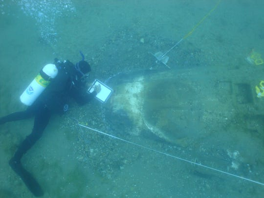 Diver Wayne Lusardi approaches the wing of a fighter plane that crashed in Lake Huron during World War II.