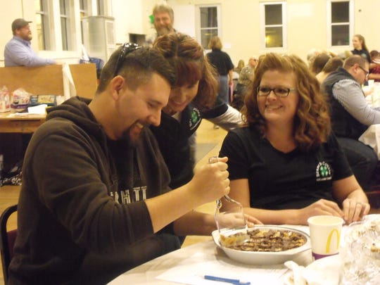 Tom Waltke wields a spatula as he gets ready to sample the pie he purchased during the Branch Coun-ty 4-H Pie Auction. To his right is Sarah Batterson (standing) and his wife Cayla.