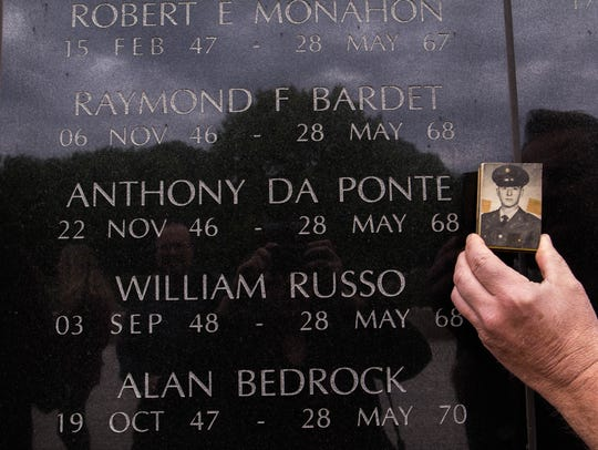George Da Ponte holds brother Anthony Da Ponte's photo next to his name at the New Jersey Vietnam Veterans Memorial in Holmdel.