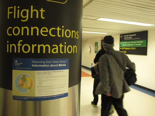 A passenger passes an Ebola warning sign in London's