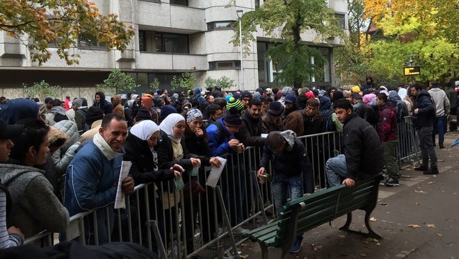 Asylum seekers wait for their applications to be processed in Berlin on Oct. 22.