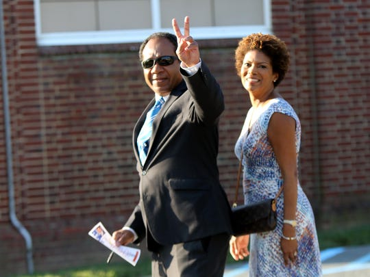 Then-Wilmington Mayor Dennis P. Williams gives a peace sign before casting his primary vote with wife, Shayne, at Harlan Elementary School on Sept. 13, 2016.