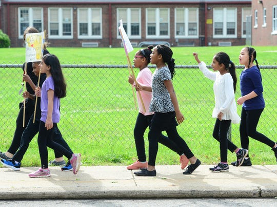 Students marched and carried signs to Tuesday's inauguration of the rainwater harvesting program near the Hawthorne School garden.