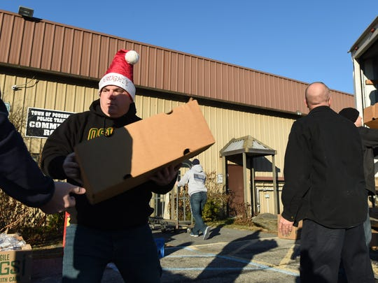Current and former law enforcement officers help pack gift boxes to be delivered to families in need during an event by the Town of Poughkeepsie Police Benevolent Association.