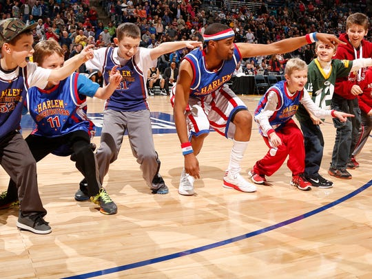 """Brawley """"Cheese"""" Chisholm is shown with young fans at a Harlem Globetrotters game. The legendary team is offering free tickets to those affected by the partial government shutdown."""