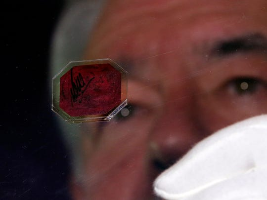 David Redden, vice chairman of Sotheby's auction house, holds the British Guiana One Cent Black on Magenta stamp in central London on June 2.