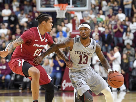Texas A&M's Duane Wilson (13) dribbles next to Arkansas' Dustin Thomas (13) during the first half of an NCAA college basketball game Tuesday, Jan. 30, 2018, in College Station, Texas. (Laura McKenzie/College Station Eagle via AP)