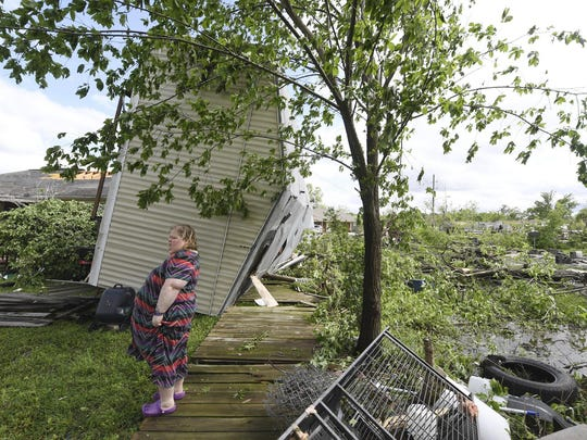 Angel Funk stands in the backyard of her Franklin, Texas, home following severe weather, Saturday, April 13, 2019. Funk's home was struck by her neighbor's mobile home, but she and her husband, who were home at the time, escaped unharmed.