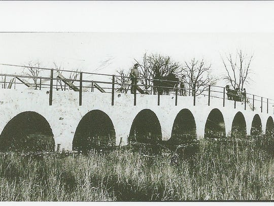The completed stone bridge, with Alphonse Halter standing