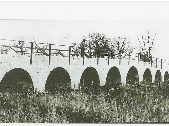 The completed stone bridge, with Alphonse Halter standing on the left.