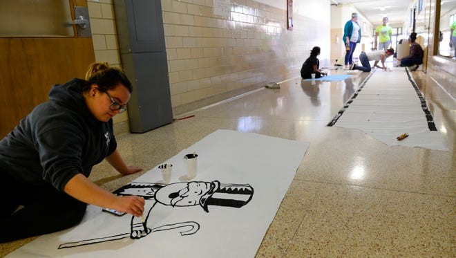 Senior Senekka Kiddey paints the Monopoly man to decorate the senior hall at Fremont Ross High School Thursday in preparation for homecoming this weekend.