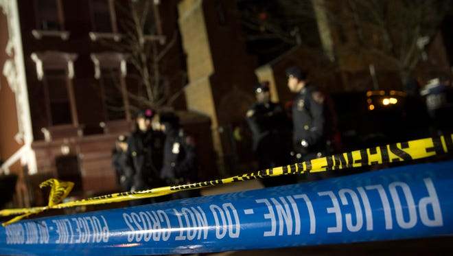 Police guard the scene where two NYPD officers were shot on Saturday.