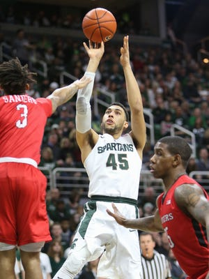 Michigan State's Denzel Valentine scores against Rutgers' Corey Sanders during the first half of MSU's 96-62 win Sunday at Breslin Center.