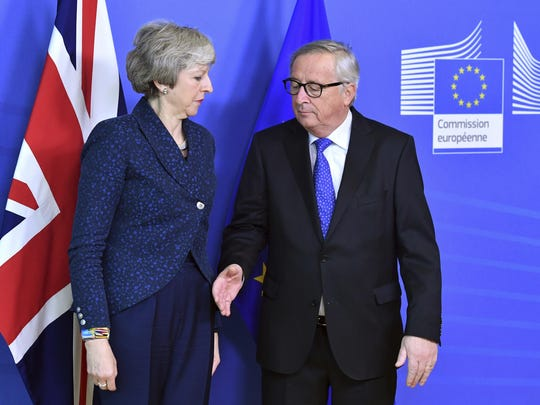 In this Feb. 7, 2019 photo European Commission President Jean-Claude Juncker, right, prepares to shake hands with British Prime Minister Theresa May, left, before their meeting at the European Commission headquarters in Brussels, Belgium.