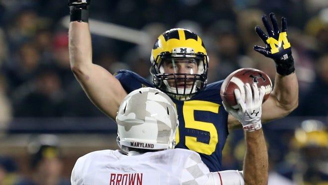 Michigan's Joe Bolden pressures Maryland's C.J. Brown (16) during second-half action on Saturday, Nov. 22, 2014, at Michigan Stadium in Ann Arbor, Mich. The visiting Terrapins won, 23-16.