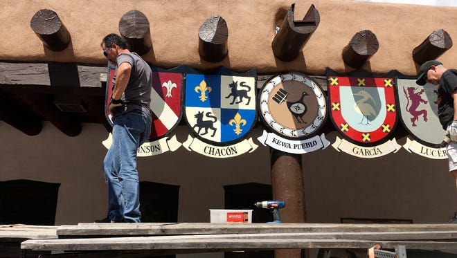 This Sept. 1, 2016 photo shows Organizers of the Santa Fe Fiesta in Santa Fe, N.M., place shields of the last names of original Spanish settler families on the Palace of the Governors while American Indian jewelers sell items below.  For centuries, northern New Mexico Hispanic residents have held an elaborate festival in Santa Fe in honor of Spanish conquistador Don Diego De Vargas' who reclaimed the city following an American Indian revolt.  But after 301 years, an emboldened group of Native American activists say it's time to change a celebration centered around the conquest of New Mexico's Pueblo tribes.