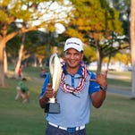 PGA golfer Fabian Gomez poses with the trophy after