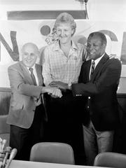 Larry Bird, center, clasps hands with Celtics general