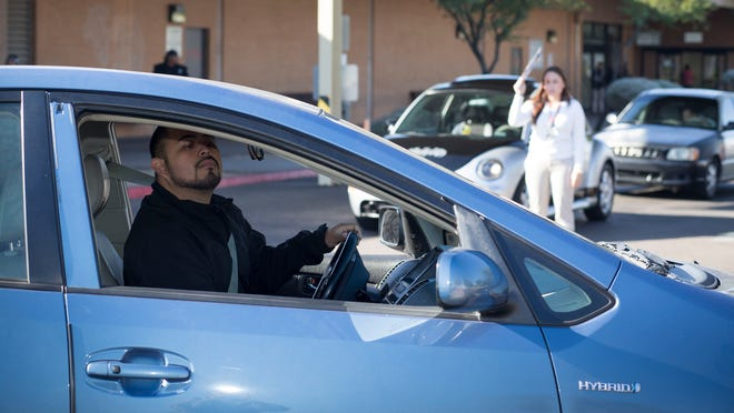 """Jaime Meza, 31, of Phoenix, attempts to parallel park during his road test in December 2014 at the Motor Vehicle Division office on North 51st Avenue in Maryvale. Meza was one of the first """"dreamers,"""" the young migrants brought to the country illegally as children, to apply for a driver's license."""