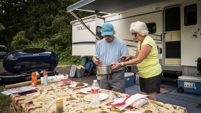 Harry and Marla Uhle work on dinner together in front of their camper before the Fourth of July weekend. They have shared a variety of campers and trailers in the 35 years they've been married. More people are taking to camping, RVs and outdoor activities as COVID-19 changes summer plans. [Dana Sparks/The Register-Guard] - registerguard.com