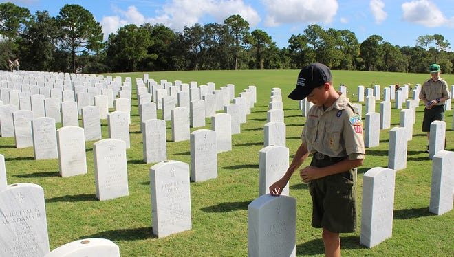 Boy Scouts place challenge coins on the headstones at Cape Canaveral National Cemetery