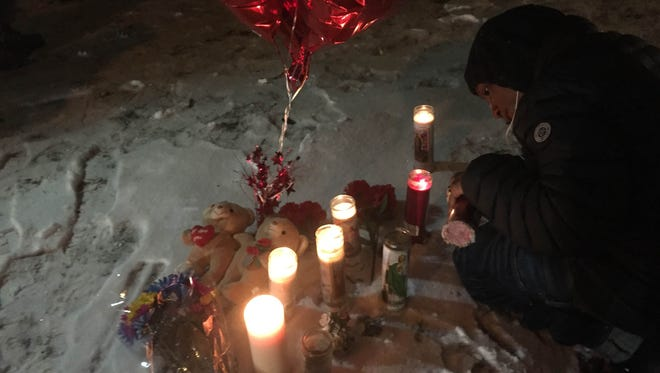 A mourner lights a candle in the darkness on Thursday in front of a Leighton Avenue home where a quadruple homicide occurred on Monday.