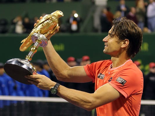 Spain's David Ferrer poses with his trophy after winning the Qatar's ExxonMobil Open in Doha, Qatar,Saturday, Jan. 10, 2015. (AP Photo/Osama Faisal)