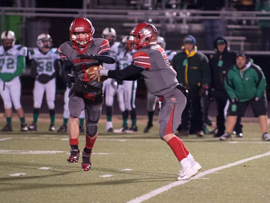 Loudonville's Kolton Edmonson hands off the ball to Austin VanSickle during their game against Mogadore Friday night in Canton.