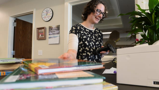 Librarian Stephanie Overbay checks books back into the system at the Jeff Reichelt Memorial Library in Big Sandy, which opened after years of planning and development.