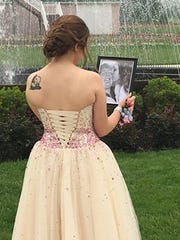 Kaylee Suders looks at a photo of her and Carter Brown, her boyfriend and 2017 James Buchanan grad who was killed in a car crash in April. Carter's dad, Robert Brown, escorted her to the prom on Saturday, May 19, 2018.