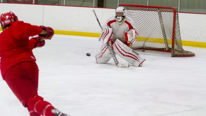 An Ithaca High hockey player takes a shot on senior goalie Keane Niday in practice on Wednesday in Lansing.