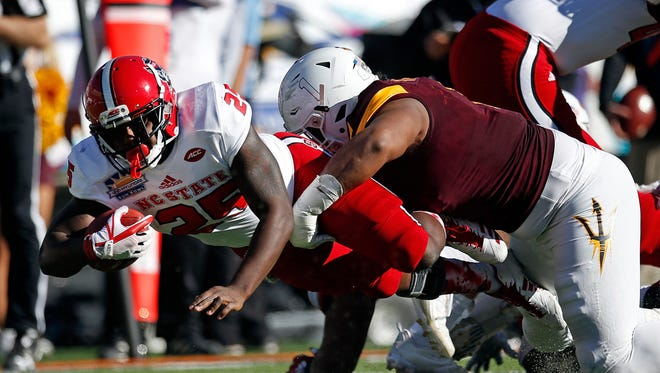 North Carolina State running back Reggie Gallaspy (25) is tackled by Arizona State defensive lineman JoJo Wicker (1) during the first half of the Sun Bowl NCAA college football game in El Paso, Texas, Friday, Dec. 29, 2017.