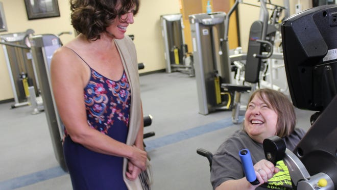 Misti Hagler, right, pauses during her workout to talk to singer Amy Grant on Thursday at the West Texas Rehabilitation Center. A year ago, Hagler met Vince Gill, Grant's husband, at the center.