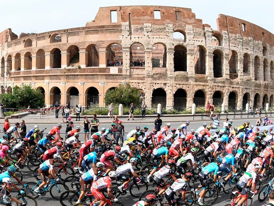 The pack of cyclists pedals past the ancient Colosseum